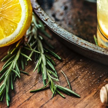 Rosemary sprig on table with lemons for lemonade.
