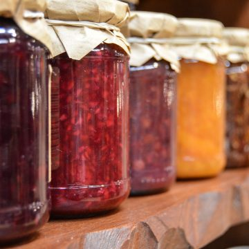 Different types of jam in jars on a counter.